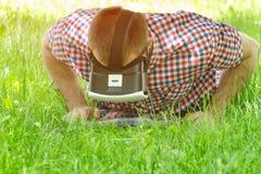 虚拟现实盔甲的人在绿草和看说谎下来 免版税库存照片