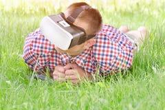 虚拟现实盔甲的人在绿草说谎 库存照片