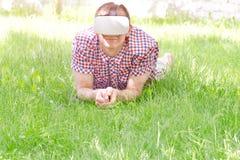 虚拟现实盔甲的人在绿草说谎 图库摄影