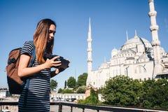 戴虚拟现实眼镜的一个旅客 真正旅行的概念环球 在背景中蓝色 免版税库存照片