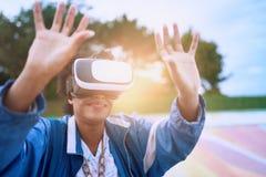 戴虚拟现实眼镜的凉快的千福年的黑人妇女,在一个滑板在一个室外冰鞋公园 库存照片