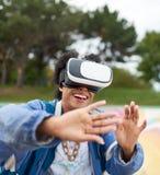 戴虚拟现实眼镜的凉快的千福年的黑人妇女,在一个滑板在一个室外冰鞋公园 免版税图库摄影