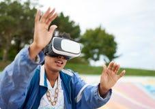 戴虚拟现实眼镜的凉快的千福年的黑人妇女,在一个滑板在一个室外冰鞋公园 免版税库存照片