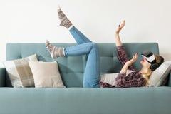 戴虚拟现实眼镜的可爱的妇女说谎在长沙发 虚拟现实耳机 生活方式虚拟现实 免版税图库摄影
