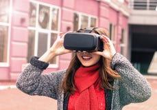 戴虚拟现实耳机或3d眼镜的美丽的女孩 免版税库存照片