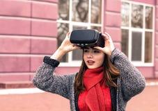 戴虚拟现实耳机或3d眼镜的美丽的女孩 免版税库存图片