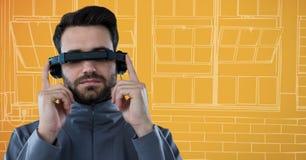 虚拟现实耳机的人反对橙色和白色手拉的窗口 免版税库存图片