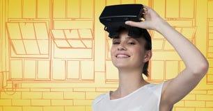 虚拟现实耳机的妇女反对黄色和橙色手拉的窗口 库存照片