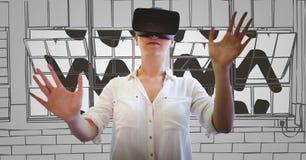 虚拟现实耳机的妇女实施反对灰色手拉的窗口 图库摄影