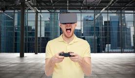 虚拟现实耳机的恼怒的人有gamepad的 免版税图库摄影