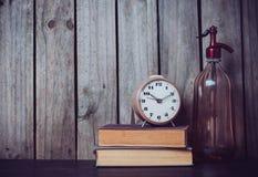 虹吸管、闹钟和葡萄酒书 免版税库存图片
