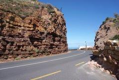 虽则美丽的路在海角点附近的红色石小山在盖帽 库存照片