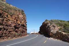 虽则美丽的路在海角点附近的红色石小山在盖帽 免版税库存图片