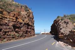 虽则美丽的路在海角点附近的红色石小山在盖帽 库存图片