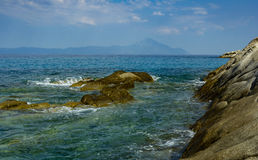 虽则被看见游泳在希腊水域中的岩石的圣山 库存图片