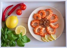 虾在板材和新鲜蔬菜,在一个美丽的盘子的果子油煎了 免版税库存图片