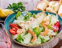虾沙拉用帕尔马干酪、油煎方型小面包片、蕃茄、混杂的绿色、莴苣和杯在木背景的酒 库存照片