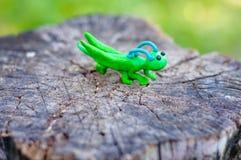 蚂蚱由彩色塑泥制成在自然本底 免版税库存图片