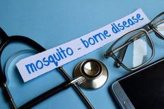蚊子传播的疾病题字有听诊器、镜片和智能手机看法在蓝色背景 免版税图库摄影