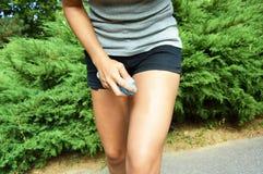 蚊子放水剂浪花 反对臭虫的女孩喷洒的杀虫剂在腿皮肤咬住室外在自然森林里使用浪花 库存图片