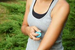 蚊子放水剂浪花 反对臭虫的妇女喷洒的杀虫剂在胳膊皮肤咬住室外在自然森林里使用浪花 免版税图库摄影