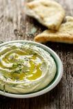 蚕豆hummus,与橄榄油、新鲜薄荷和芝麻籽的加法 库存图片