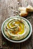 蚕豆hummus,与橄榄油、辣椒粉粉末、新鲜薄荷和芝麻籽的加法 免版税库存图片