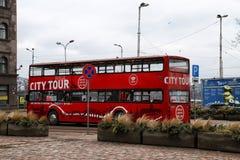 蛇麻草在蛇麻草城市观光旅游公共汽车的旅游红色双层甲板船在里加市街道上  免版税库存图片