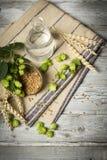 蛇麻草花、麦子耳朵和种子,水 酿造啤酒的成份在木桌上 库存照片