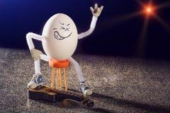 蛋摇摆物吉他弹奏者坐椅子 库存照片