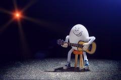 蛋有声学吉他的摇摆物吉他弹奏者 库存图片