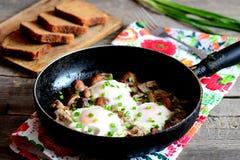 蛋炸锅 有机鸡蛋油煎了用蘑菇和葱 黑面包切片,叉子,新鲜的葱 库存图片