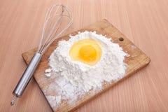 蛋白和卵黄质在地板在厨房用桌上 库存照片