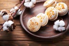 蛋白杏仁饼干和棉花花在木桌上 免版税图库摄影