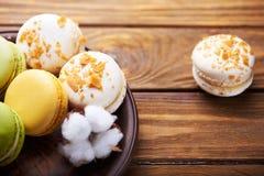 蛋白杏仁饼干和棉花花在木桌上 免版税库存图片