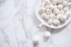 蛋白甜饼曲奇饼在一块白色大理石的一块板材 库存照片