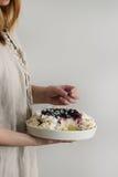 蛋白甜饼蛋糕帕夫洛娃在女性手上 库存图片
