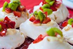 蛋白甜饼Pavlovas用草莓和猕猴桃顶部 库存图片