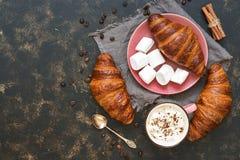 蛋白软糖、咖啡和新鲜的新月形面包在黑暗的背景 顶视图,拷贝空间 正餐鱼食物法语表 免版税图库摄影
