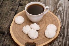 蛋白软糖和杯子咖啡在一棵树的锯裁减在木 免版税库存图片