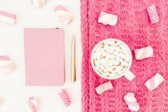 蛋白软糖的秀丽桃红色概念与热奶咖啡杯子、布料、笔和笔记本的在白色背景 平的位置,顶视图 图库摄影