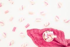 蛋白软糖的秀丽桃红色概念与热奶咖啡杯子和布料的在白色背景 平的位置,顶视图 免版税库存照片