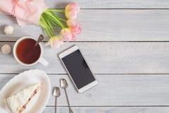 蛋糕、电话、茶和在白色木桌上的桃红色郁金香 免版税库存照片