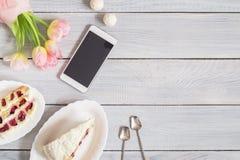 蛋糕、电话和桃红色郁金香在白色木桌上 免版税库存图片