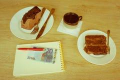 蛋糕、笔记薄、金钱和咖啡在桌上 库存图片