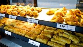 蛋糕、面包和小圆面包在架子 免版税库存图片