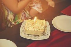 蛋糕与一个灼烧的蜡烛的在桌上的一块白色板材在咖啡馆 生日 免版税库存图片