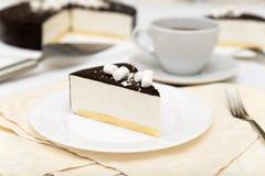 蛋糕与蛋白牛奶酥`鸟` s牛奶`、饼干、奶油甜点和黑暗的巧克力的在一块白色板材 免版税库存照片