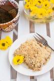 蛋糕与面包屑、茶和黄色的在白色woode开花 免版税库存照片