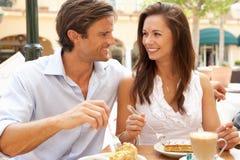 蛋糕享用年轻人的咖啡夫妇 图库摄影